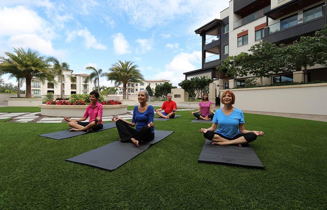 moorings park residents performing outdoor yoga in Naples, Florida