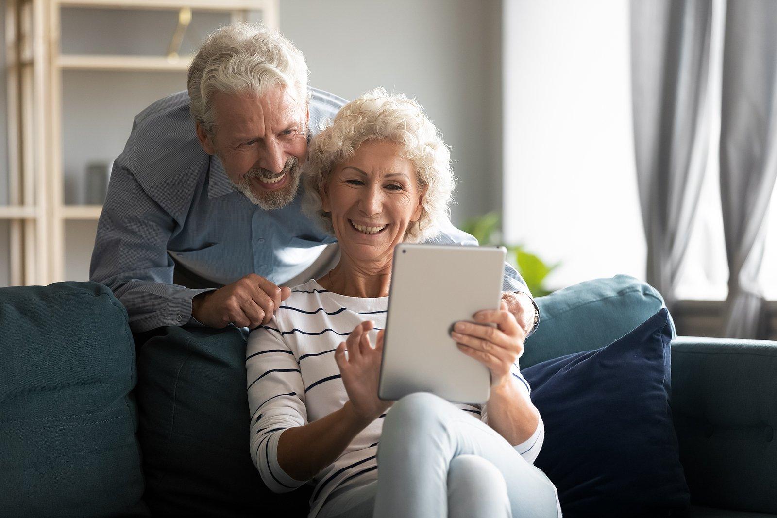 bigstock-Happy-Older-Couple-Using-Compu-360928888
