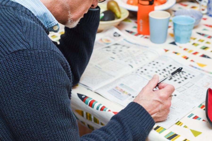 man doing crossword puzzle for seniors