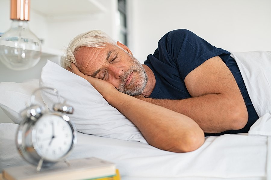 bigstock-Old-tired-man-sleeping-on-bed--363994525