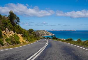 road along cliff and seaside blue sky clouds