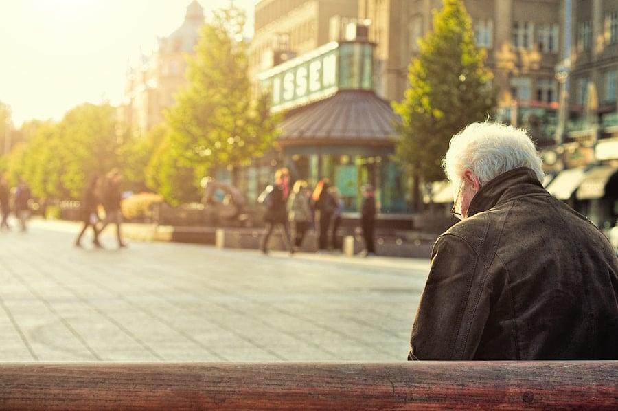 senior on bench in city